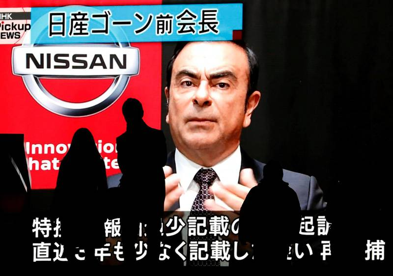 FILE PHOTO: Passersby are silhouetted as a huge street monitor broadcasts news reporting ousted Nissan Motor chairman Carlos Ghosn's indictment and re-arrest in Tokyo, Japan December 10, 2018.  REUTERS/Issei Kato/File Photo