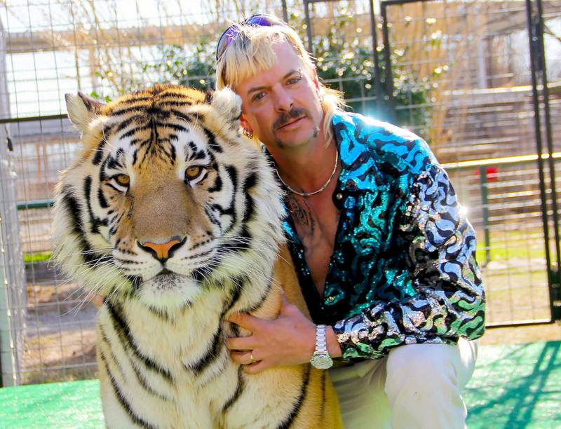 """This undated photo courtesy of Netflix shows Joseph """"Joe Exotic"""" Maldonado-Passage with one of his tigers. Amid a constant swirl of grim coronavirus news, the surreal tale of a gay, mullet-wearing private zookeeper who calls himself """"Joe Exotic"""" --  now in prison for murder-for-hire -- has captivated a nation stuck on the couch.  """"Tiger King: Murder, Mayhem and Madness"""" -- featuring a menagerie of big cats, wacky employees and misfit lovers -- is part """"Animal Planet"""" and part """"Breaking Bad."""" And it's all true. - RESTRICTED TO EDITORIAL USE - MANDATORY CREDIT """"AFP PHOTO / NETFLIX"""" - NO MARKETING - NO ADVERTISING CAMPAIGNS - DISTRIBUTED AS A SERVICE TO CLIENTS  / AFP / Netflix US / - / RESTRICTED TO EDITORIAL USE - MANDATORY CREDIT """"AFP PHOTO / NETFLIX"""" - NO MARKETING - NO ADVERTISING CAMPAIGNS - DISTRIBUTED AS A SERVICE TO CLIENTS"""