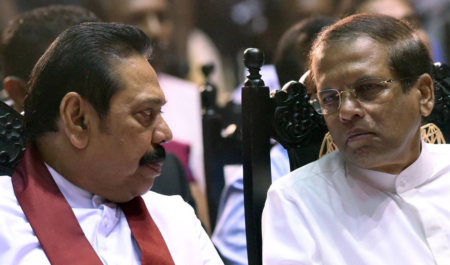 Sri Lanka's President Maithripala Sirisena (R) listens to former president and currently appointed Prime Minister Mahinda Rajapakse attend a ceremony granting employment to social service workers, in Colombo on November 30, 2018.  Rajapakse was controversially named prime minister last month, but the parliament has in two votes toppled him in no-confidence motions which he and Sirisena are refusing to accept causing a deepening political crisis. / AFP / ISHARA S.  KODIKARA