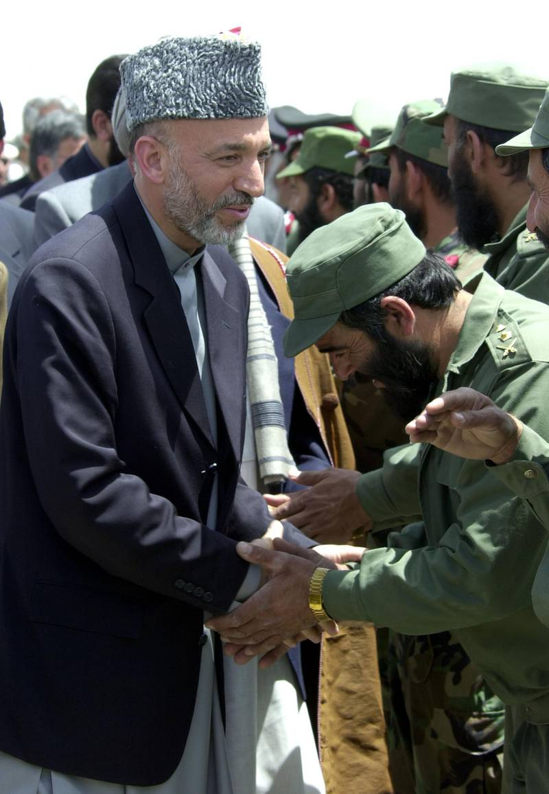 404929 03: Interim Afghan leader Hamid Karzai (L) is greeted by a group of Afghan military officers on his arrival to Kandahar airbase May 04, 2002 in Southern Afghanistan. The visit by Karzai to the city, his first since assuming power, is significant because of the city's history as a former Taliban stronghold. (Photo by Scott Nelson/Getty Images)