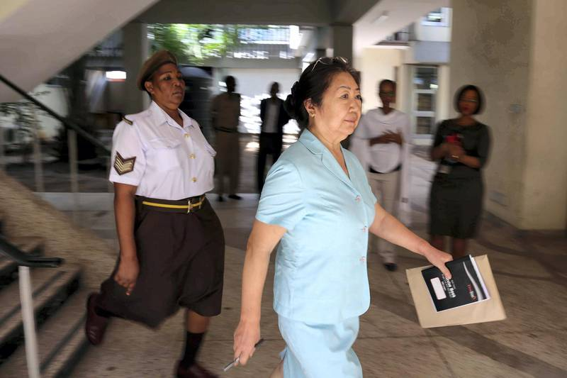 """The 66-year-old, Yang Fenglan, is being escorted by Tanzania's Prison warden as she was brought at Kisutu Resident's Magistrate Court in Dar es Salaam, Friday November 04, 2016. - The Chinese woman nicknamed the """"Ivory Queen"""" who is accused of leading one of Africa's biggest ivory smuggling rings, responsible for more than 700 elephant tusks worth $2.5m (£1.7m) illegally leaving Tanzania for the Far East, was brought to the court for the case hearing. However the court has adjoined the hearing until November 15, 2016, due to the absence of the prosecution's first witness. (Photo by Said KHALFAN / AFP)"""