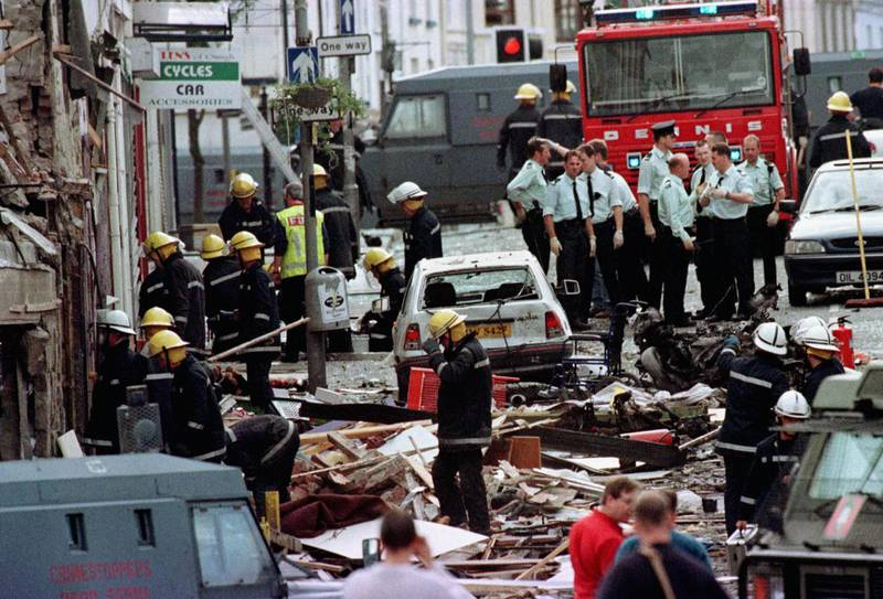 Royal Ulster Constabulary police officers and firefighters inspect the damage caused by a bomb explosion in Market Street, Omagh,  Co Tyrone, Northern Ireland, 72 miles west of Belfast. PA PHOTO PAUL MCERLANE   (Photo by Paul McErlane - PA Images/PA Images via Getty Images)