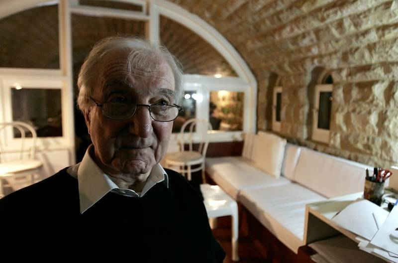 """Iraqi architect Rifat Chadirji is pictured at his home office in the Lebanese coastal town of Halat on April 24, 2009. Two decades before US marines pulled down a statue of Saddam Hussein in a Baghdad square, the dictator destroyed a monument in the same place, the magnum opus of one of Iraq's greatest architects. The elegant arch entitled """"The Unknown Soldier"""" was a Baghdad landmark for more than 20 years. Now its builder, Rifat Chadirji, has returned to rebuild it in the hope of resurrecting some of his beloved city's former glory. AFP PHOTO/JOSEPH EID (Photo by JOSEPH EID / AFP)"""