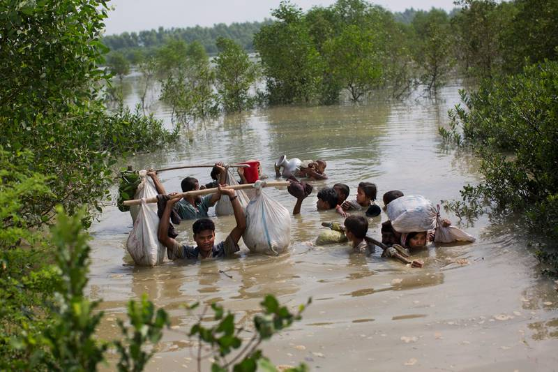 A Rohingya family reaches the Bangladesh border after crossing a creek of the Naf river on the border with Myanmmar, in Cox's Bazar's Teknaf area, Monday, Sept. 4, 2017. (AP Photo/Bernat Armangue)