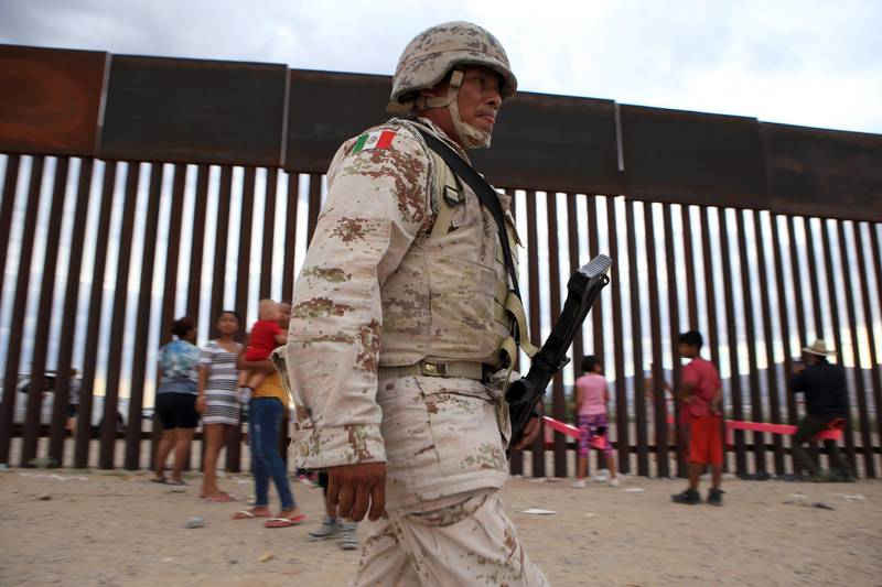 """A mexican soldier walks in front of American and Mexican families playing with a toy called """"up and down"""" (Seesaw swing) over the Mexican border with US at the Anapra zone in Ciudad Juarez, Chihuahua State, Mexico on July 28, 2019. (Photo by LUIS TORRES / AFP)"""
