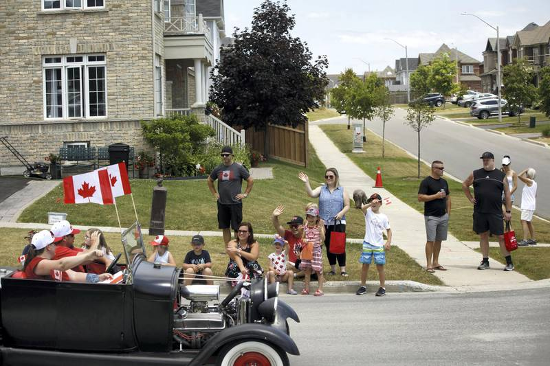 NEWCASTLE, ON - JULY 01: People watch from street corner as a passing Canada Day drive-by parade makes its way through town on July 1, 2020 in Newcastle, Canada. While most events marking the 153rd anniversary of Confederation across the country have been cancelled or moved online due to the spread of the coronavirus, the village of Newcastle encouraged residents to celebrate from their homes as a drive-by parade snaked through the village in order to comply with social distancing measures.   Cole Burston/Getty Images/AFP