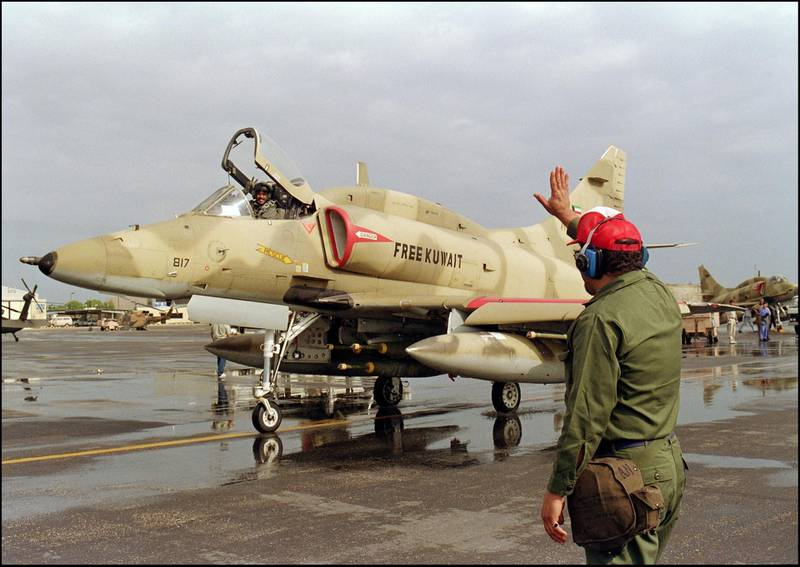 """A Kuwaiti airfield worker waves to a departing of a Kuwaiti Air Force A-4 US-made Skyhawk jet fighter pilot 24 January 1991 leaving the Al Hasra air base for a bombing mission over Iraq. Iraq's invasion of Kuwait 02 August 1990, ostensibly over violations of the Iraqi border, led to the Gulf War which began 16 January 1991. A US-led multi-national force expelled Iraq from Kuwait during the """"Desert Storm"""" offensive and a cease-fire was signed 28 February 1991. (Photo by CHRIS WILKINS / AFP)"""