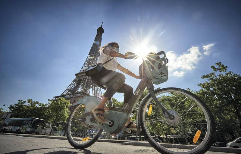 PARIS, FRANCE - AUGUST 04: A cyclist rides past the Eiffel Tower on one of the 20,000 Velib rental bikes available in Paris on August 04, 2020 in Paris, France. Since the end of lockdown the number of cyclists in Paris has risen by nearly 50 percent as authorities have encouraged cycling as a safer, and more environmentally friendly form of transport away from crowded buses and metro trains as they continue to try to halt the spread of COVID-19. Mayor Anne Hidalgo has added a further 31 miles of roadway in the city for bikes with the promise of making Paris a cycling capital.  (Photo by Kiran Ridley/Getty Images)