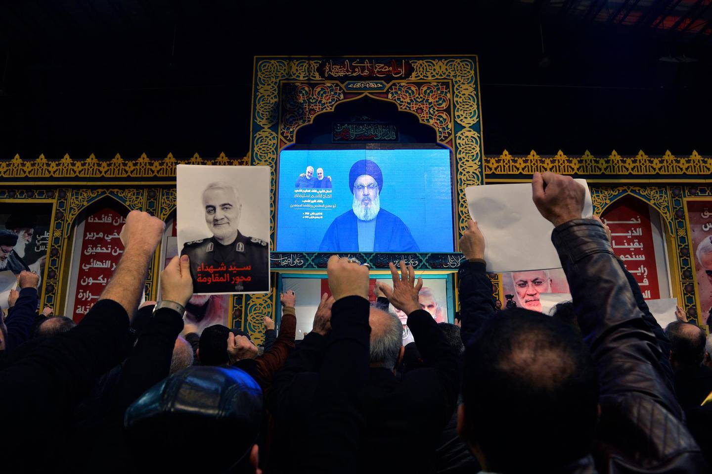 epa08104470 Supporters of Hezbollah listen to Hezbollah's Secretary-General Sayed Hassan Nasrallah as he delivers a speech on a screen during a mass rally to pay tribute the Iranian Revolutionary Guards Corps (IRGC) Lieutenant general and commander of the Quds Force Qasem Soleimani in the southern suburb of Beirut, Lebanon, 05 January 2020. The US Pentagon announced that Iran's Quds Force leader Soleimani and Iraqi militia commander Abu Mahdi al-Muhandis were killed on 03 January 2020 following a US airstrike at Baghdad's international airport. The attack comes amid escalating tensions between Tehran and Washington.  EPA/WAEL HAMZEH