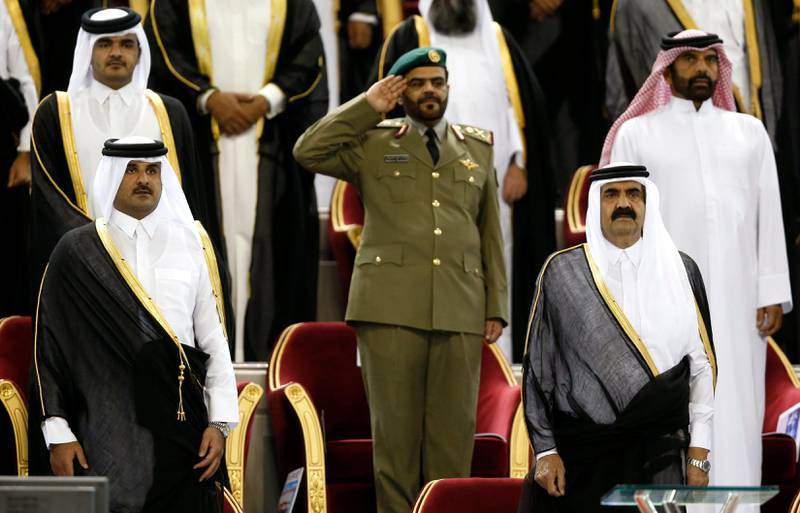 Qatar's Emir Sheikh Hamad bin Khalifa al-Thani (R) stands next to his son Crown Prince Sheikh Tamim before the Emir Cup final match between Al-Sadd and Al-Rayyan at Khalifa stadium in Doha in this May 18, 2013 file photo. The emir of Qatar told his family on June 24, 2013 he would hand power to his son, al Jazeera reported, preparing the wealthy gas-exporting Gulf Arab country for a highly unusual step in a region where hereditary rule normally means for life. REUTERS/Fadi Al-Assaad/Files (QATAR - Tags: ROYALS POLITICS) *** Local Caption ***  QAT04_QATAR-EMIR-_0624_11.JPG