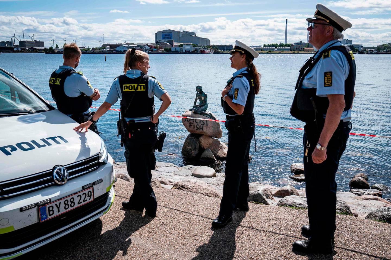 "Policemen stand on July 3, 2020 in front of the ""Little Mermaid"" sculpture after it has been vandalised in Copenhagen.  - Denmark OUT  / AFP / Ritzau Scanpix / Niels Christian Vilmann"