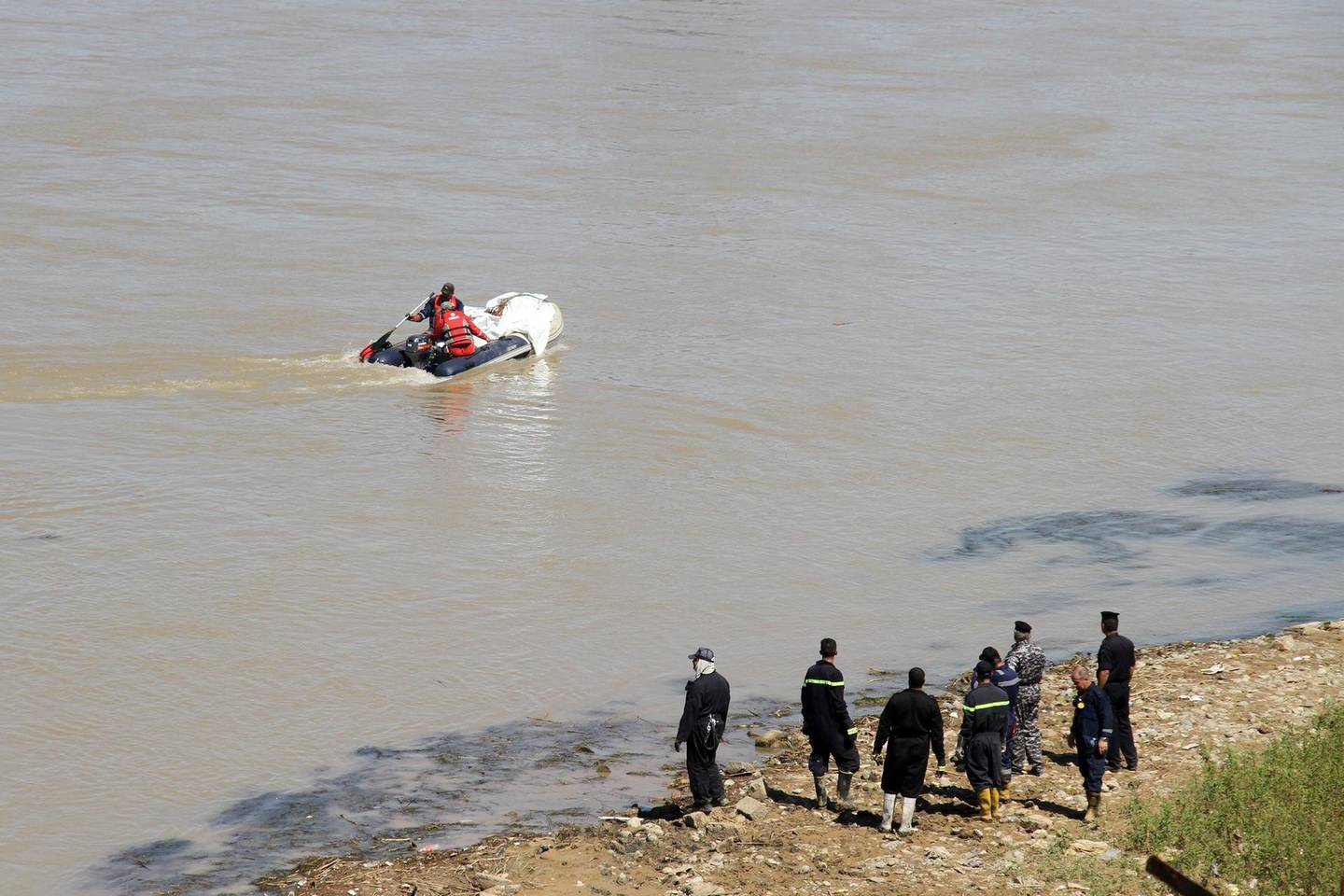 Iraqi civil defence recover a body from the Tigris river in the northern Iraqi city of Mosul on May 16, 2018.  Some 10 months after dislodging the Islamic State group, fire crews and police are still extracting bodies from the ruins of the shattered Old City. / AFP / Waleed AL-KHALID