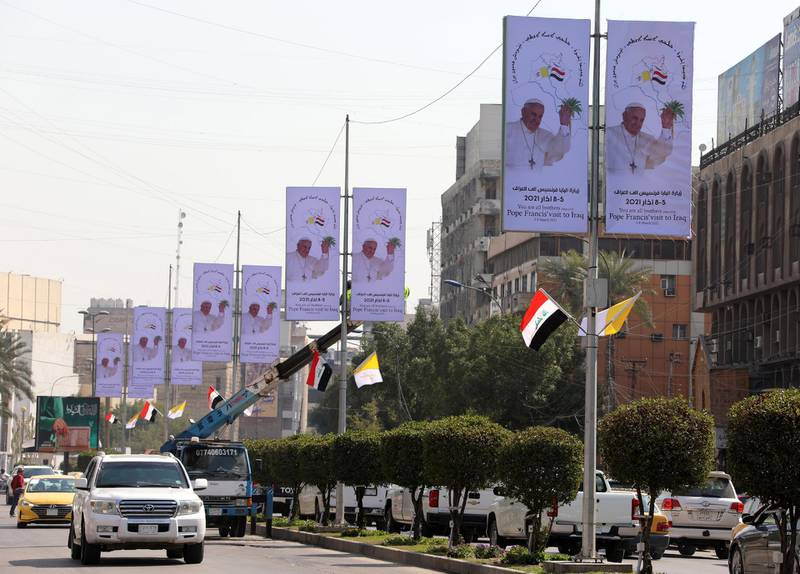epa09045264 Iraqi workers hang up posters as well as Iraqi and Vatican flags to welcome Pope Francis at a street in central Baghdad, Iraq, 01 March 2021. Pope Francis will be in Iraq for an Apostolic Visit from 05 to 08 March 2021, during which he will pay a courtesy visit to the President and meet with civil authorities and members of the Diplomatic Corps. The Pontiff is scheduled to celebrate Holy Mass at the Chaldean Cathedral of Saint Joseph in Baghdad on Saturday, 06 March 2021.  EPA/AHMED JALIL