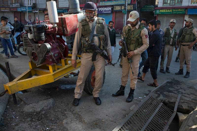 Indian policemen and locals inspect the site of an explosion in Srinagar, Indian controlled Kashmir, Saturday, Oct. 12, 2019. At least seven pedestrians were wounded on Saturday in Indian portion of Kashmir in a grenade explosion, according to authorities. (AP Photo/ Dar Yasin)