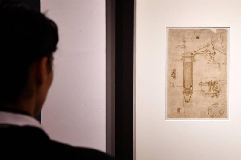 """A visitor watches Leonardo da Vinci's """"Study for a hydraulic pump, man with a perspectograph (Codex Atlanticus)"""" during the exhibition """"Science Before Science"""" (La Scienza prima della Scienza) on March 12, 2019 at the Scuderie del Quirinale palace in Rome. / AFP / Alberto PIZZOLI"""