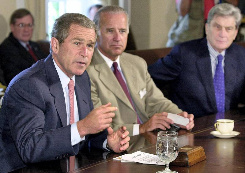 US President George W. Bush (L) answers reporter's questions prior to a bipartisan meeting with congressional leaders in the Cabinet Room of the White House, 25 July 2001.  Listening are Senator Joe Biden (C) D-DE and Senator John Warner (R-VA).      AFP PHOTO/Mike THEILER (Photo by MIKE THEILER / AFP)