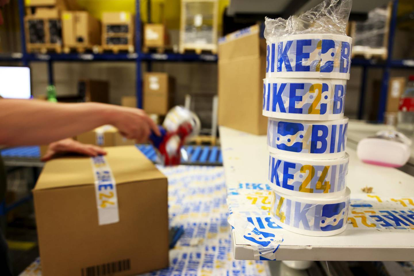 A worker seals a shipping box with adhesive tape at the Bike24 Holding AG logistics center in Dresden, Germany, on Tuesday, June 8, 2021. Bike24 is preparing to list on the Frankfurt Stock Exchange. Photographer: Liesa Johannssen-Koppitz/Bloomberg