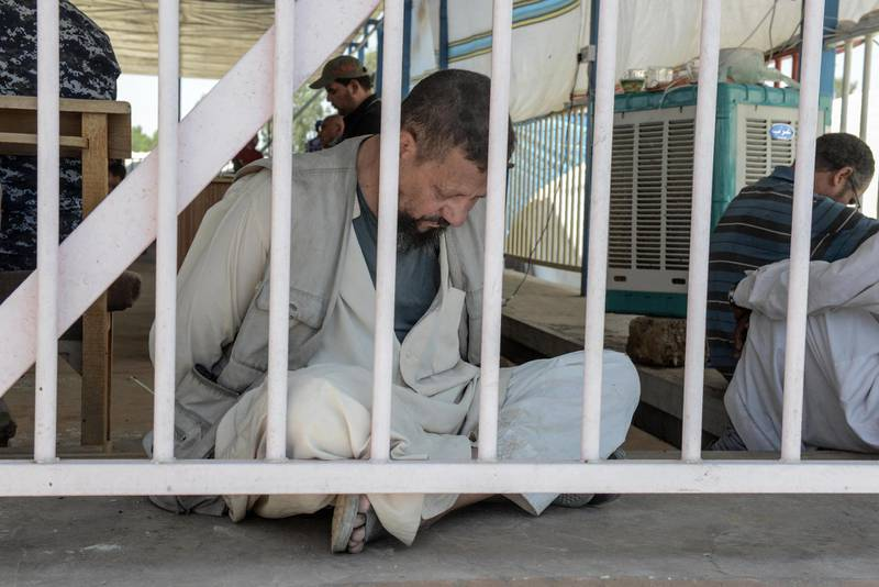 A man suspected of being an Egyptian member of the Islamic State group is detained by Iraqi soldiers at a temporary camp in the compound of the closed Nineveh International Hotel in Mosul on June 16, 2017 which was recovered by Iraqi troops from IS fighters earlier in the year. - A screening centre set up in the compound's fairgrounds sees a constant stream of Iraqis fleeing the battle for Mosul, awaiting their turn to be checked by the Iraqi forces who are searching for suspected Islamic State (IS) group members.The small fairground lies at the end of a pontoon bridge across the Tigris recently opened to civilians that is the only physical link between the two banks of the river. (Photo by MOHAMED EL-SHAHED / AFP)