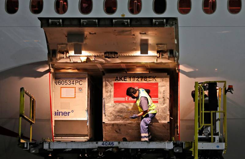 A Pfizer-BioNTech COVID-19 coronavirus vaccines shipment is offloaded from an Emirates Airlines Boing 777 arrived from Brussels at Dubai International Airport in Dubai, United Arab Emirates, Saturday, Feb. 20, 2021. As the coronavirus pandemic continues to clobber the aviation industry, Emirates Airlines, the Middle East's biggest airline is seeking to play a vital role in the global vaccine delivery effort. (AP Photo/Kamran Jebreili)