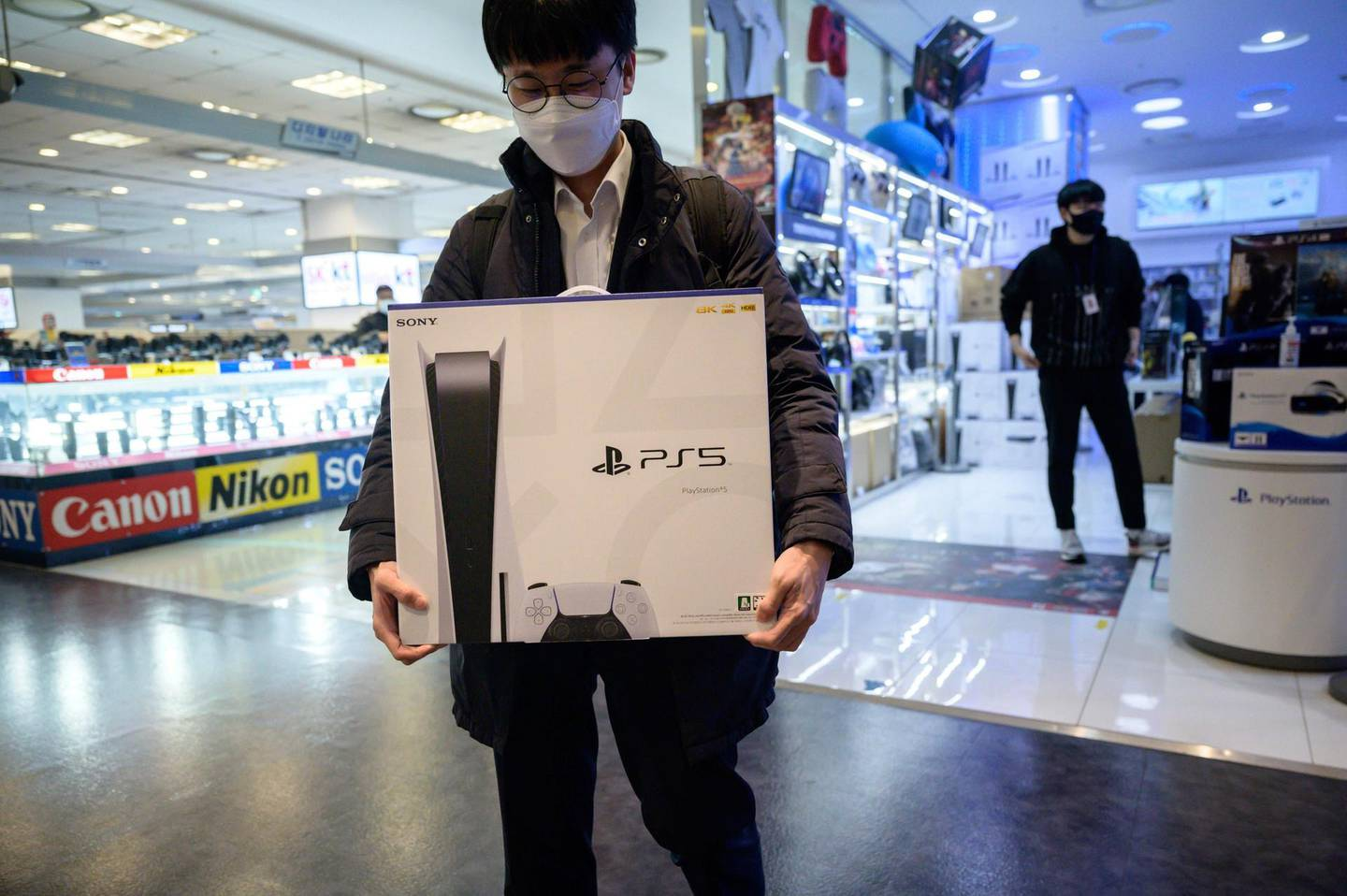 In a photo taken on November 12, 2020, a customer walks away after purchasing the new Sony Playstation PS5 in Seoul after Sony launched the new console in select markets around the world.  / AFP / Ed JONES
