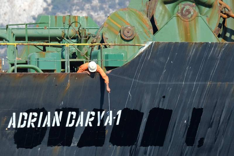 """(FILES) In this file photo taken on August 18, 2019 a crew member checks the new name of Iranian oil tanker Adrian Darya, formerly known as Grace 1, off the coast of Gibraltar. The United States on August 30, 2019, sanctioned an Iranian oil tanker previously held for weeks by Gibraltar and released despite Washington's efforts to keep it detained. The US Department of Treasury said the vessel, previously known as the Grace 1, is """"blocked property"""" under an anti-terrorist order, and """"anyone providing support to the Adrian Darya 1 risks being sanctioned.""""  / AFP / Johnny BUGEJA"""