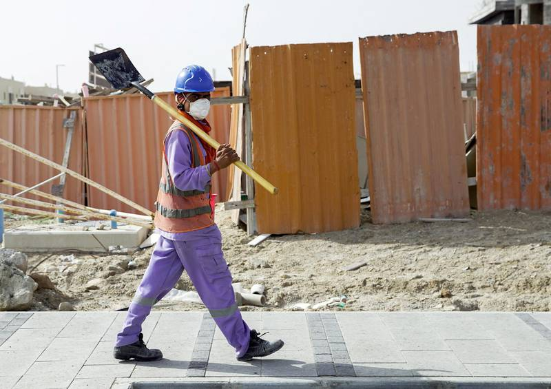 Abu Dhabi, United Arab Emirates, April 5, 2020.  A construction worker crosses the street with a mask on at Khalifa City, Abu Dhabi.  Face masks should be worn at all times when outside the home, the UAE government said on Saturday.              Victor Besa / The NationalSection:  NAReporter: