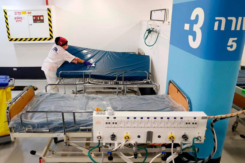 A worker cleans a bed mattress in the underground parking of Rambam Health Care Campus which was transformed into an intensive care facility for coronavirus patients, in the northern Israeli city of Haifa on September 23, 2020. Authorities in Israel, which has seen one of the world's highest per capita rates of novel coronavirus infections in the past two weeks, imposed a new nationwide lockdown on September 18. / AFP / JACK GUEZ