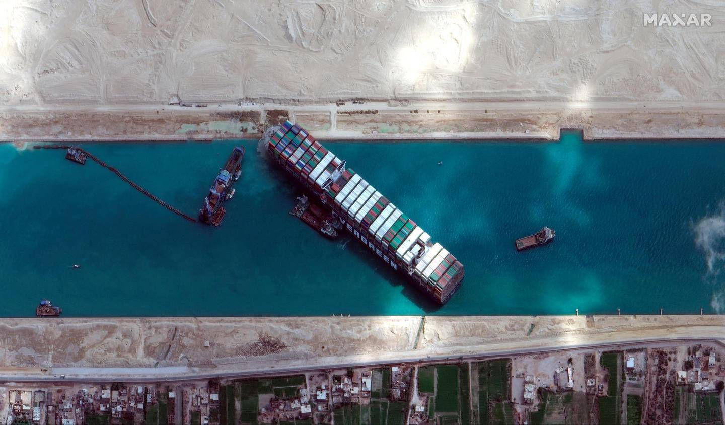 This satellite image from Maxar Technologies shows the cargo ship MV Ever Given stuck in the Suez Canal near Suez, Egypt, Sunday, March 28, 2021. Two additional tugboats sped Sunday to Egypt's Suez Canal to aid efforts to free the skyscraper-sized container ship wedged for days across the crucial waterway, even as major shippers increasingly divert their boats out of fear the vessel may take even longer to free. (©Maxar Technologies via AP)