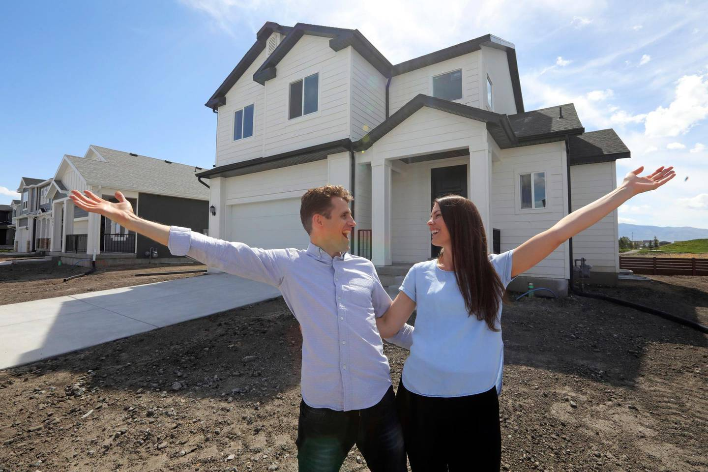 In this April 27, 2019, photo, Andy and Stacie Proctor stand in front of their new home in Vineyard, Utah. For some millennials looking to buy their first home, the hunt feels like a race against the clock. The Proctors ultimately made a successful offer on a three-bedroom house for $438,000 in Vineyard. (AP Photo/Rick Bowmer)