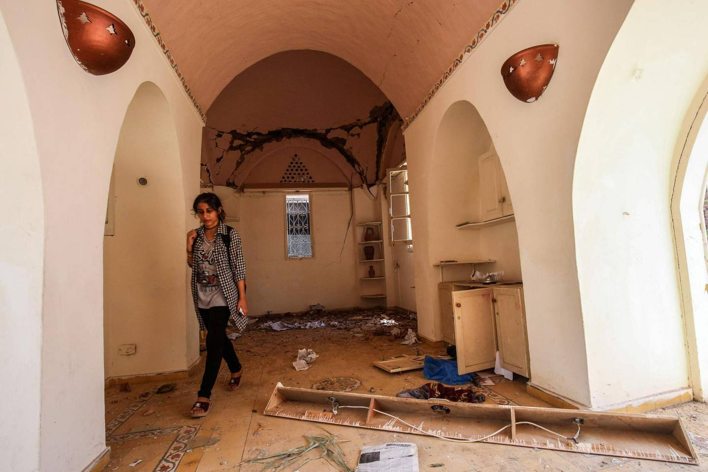 A Palestinian woman inspects damages in the showroom of Gaza the Arts and Crafts Village, adjacent to a building that was hit by Israeli air strikes two days earlier in Gaza City, on July 16, 2018. / AFP / SAID KHATIB