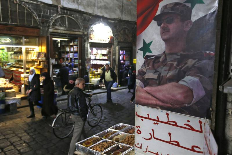 """A picture of Syrian President Bashar al-Assad decorates the al-Buzuriya market in the Old City of the Syrian capital Damascus on February 12, 2020. Syrian regime forces today pushed on with their offensive in the country's northwest, securing areas along a key national highway they seized, as tensions spiralled with Turkey which supports rebel groups. After a series of tit-for-tat attacks, Turkish President Recep Tayyip Erdogan threatened to strike Syrian regime forces """"everywhere"""" if his soldiers are harmed and accused Damascus ally Russia of committing """"massacres"""".  / AFP / LOUAI BESHARA"""
