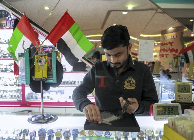 Abu Dhabi, U.A.E., November 26, 2018.  Preparations for Emirates National Day. -- Mohammed Sakeer proudly displays the U.A.E. flag on top of his watch display.Victor Besa / The NationalSection:  SPReporter: Amith Passela