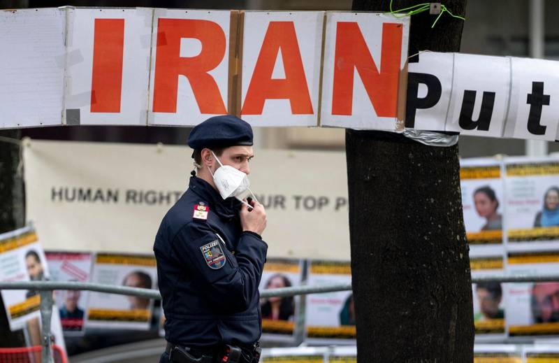 A police officer patrols in front of banners put up by members of the National Council of Resistance of Iran, an Iranian opposition group, in front of the 'Grand Hotel Wien' during the closed-door nuclear talks with Iran in Vienna on April 27, 2021, where diplomats of the UK, EU, China, Russia and Iran hold their talks. A third round of negotiations opens on April 27 in Vienna in an attempt to salvage the Iran nuclear deal, a new stage in the rocky discussions to get Iran and the United States back on track.   / AFP / JOE KLAMAR