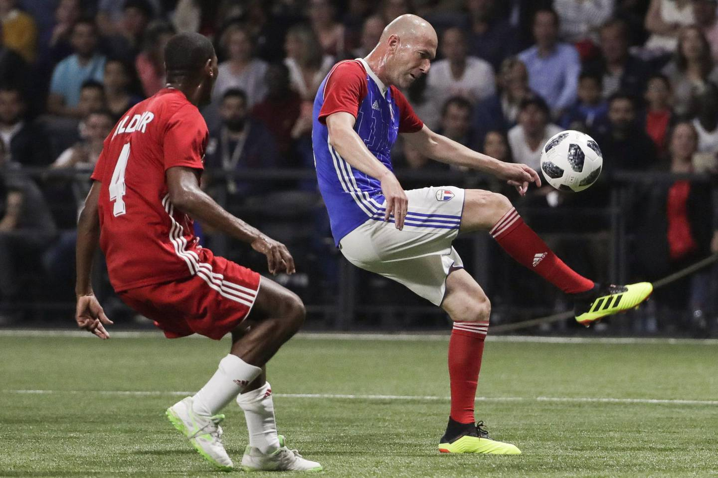 TOPSHOT - France 98's midfielder Zinedine Zidane (R) controls the ball next to Fifa 98's defender Aldair during an exhibition football match between France's 1998 World Cup's French football national team and FIFA 98 composed with former international players, to mark the 20th anniversary of France's 1998 World Cup victory, on June 12, 2018 at the U Arena in Nanterre, near Paris. / AFP / Thomas SAMSON