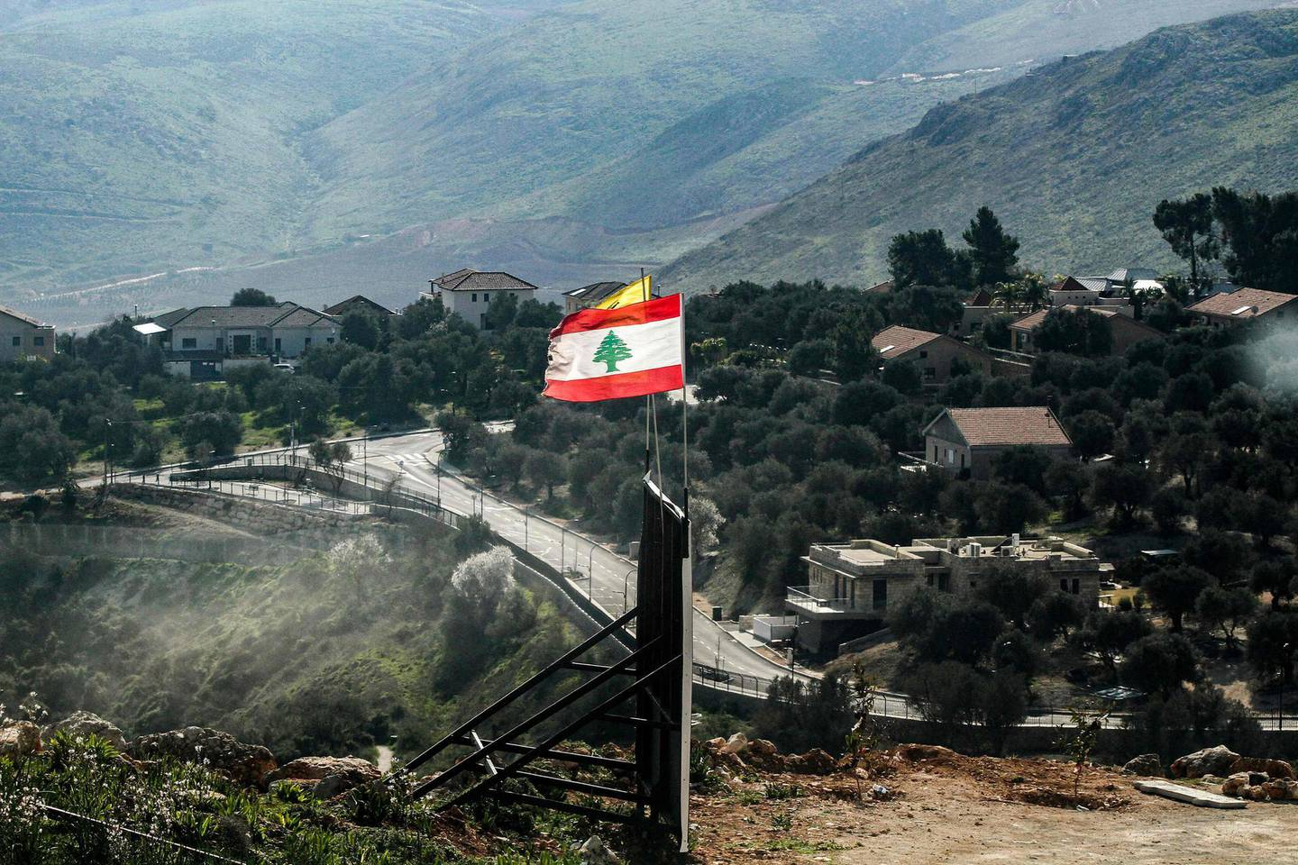 This picture taken on February 15, 2021 shows (foreground) flags of Lebanon and Lebanese Shiite movement Hezbollah (yellow) flying in Lebanon's southern plain of Marjayoun along the border with the northern Israeli town of Metulla (R).  / AFP / Mahmoud ZAYYAT