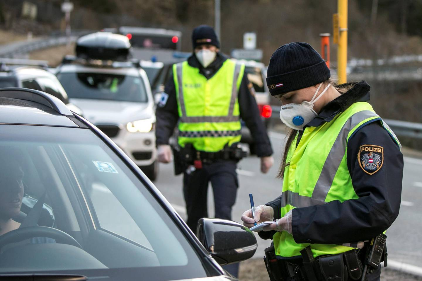ISCHGL, AUSTRIA - MARCH 13: A police officer at a roadblock asks the driver of a car driving out of the Panznautal valley for a drive through permission following the imposition of a quarantine due to the coronavirus on March 14, 2020 near Ischgl, Austria. The ski resort towns of Sankt Anton and Ischgl are both under quarantine and many ski resorts in the region have been closed. The Austrian government is pursuing aggressive measures, including closing schools, cancelling events and shuttering shops except for grocery stores and pharmacies in an effort to slow the ongoing spread of the coronavirus. (Photo by Jan Hetfleisch/Getty Images)