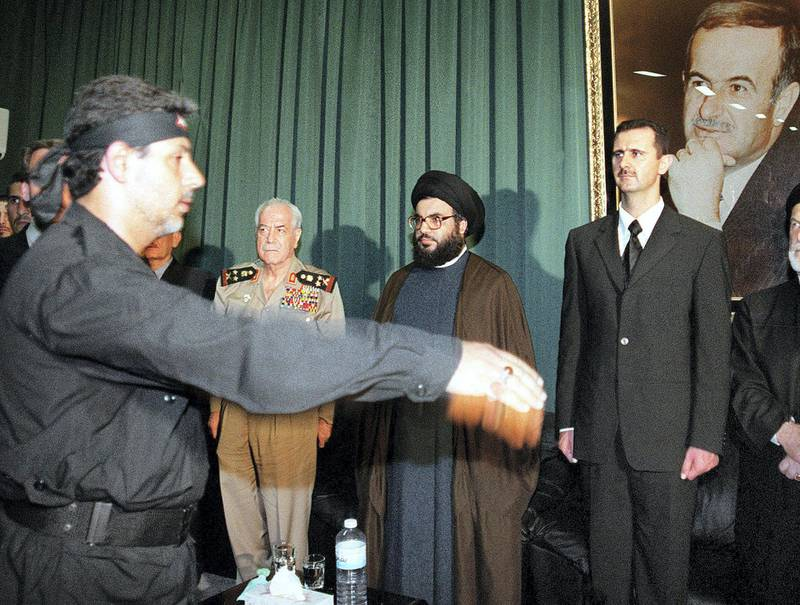 (FILES) In this file photo taken on June 16, 2000, a member of the Shiite Muslim Lebanese Hezbollah group  march past his leader, Sheikh Hassan Nasrallah (C), flanked by Syrian heir apparent Bashar al-Assad (R) and Syrian Defence Minister Mustafa Tlass in Qerdaha as members of Hezbollah offer condolences over the death of President Hafez al-Assad (picture), in the northern city of Qerdaha. - President Bashar al-Assad, whose family has ruled Syria for over half a century, faces an election this week meant to cement his image as the only hope for recovery in the war-battered country, analysts say. (Photo by - / AFP)