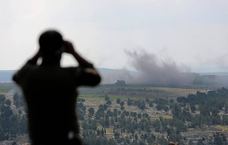 epa06600953 A Turkey-backed Free Syrian Army soldier watches with binoculars as smoke rises after a bomb attack during an offensive, at Der Mismis Village, southeast of Afrin, Syria, 13 March 2018. According to media reports, the Turkish army and its allied Syrian militias on 10 March continued to encircle the city of Afrin in the Kurdish-held enclave of the same name in northwest Syrian, taking control of nine towns. The Turkish army on 20 January launched 'Operation Olive Branch' in Syria's northern regions against the Kurdish Popular Protection Units (YPG) forces and the Syrian Democratic Forces (SDF) which control the city of Afrin. Turkey classifies the YPG as a terrorist organization. The Turkish-backed Free Syrian Army is an armed rebel military group that operates in northern Syria and is supported by the Turkish army.  EPA/STR