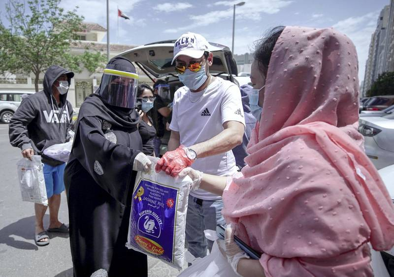 Abu Dhabi, United Arab Emirates, May 1, 2020.    Laid off Filipino Muslim workers with their rice, eggs, cooking oil and other daily essentials given to them by Filipino-Emirati woman, Mona Mohamed Baraguir at the residential area in front of Al Wahda Mall, on a Friday morning.Victor Besa / The NationalSection:  NAReporter:  Shireena Al Nuwais