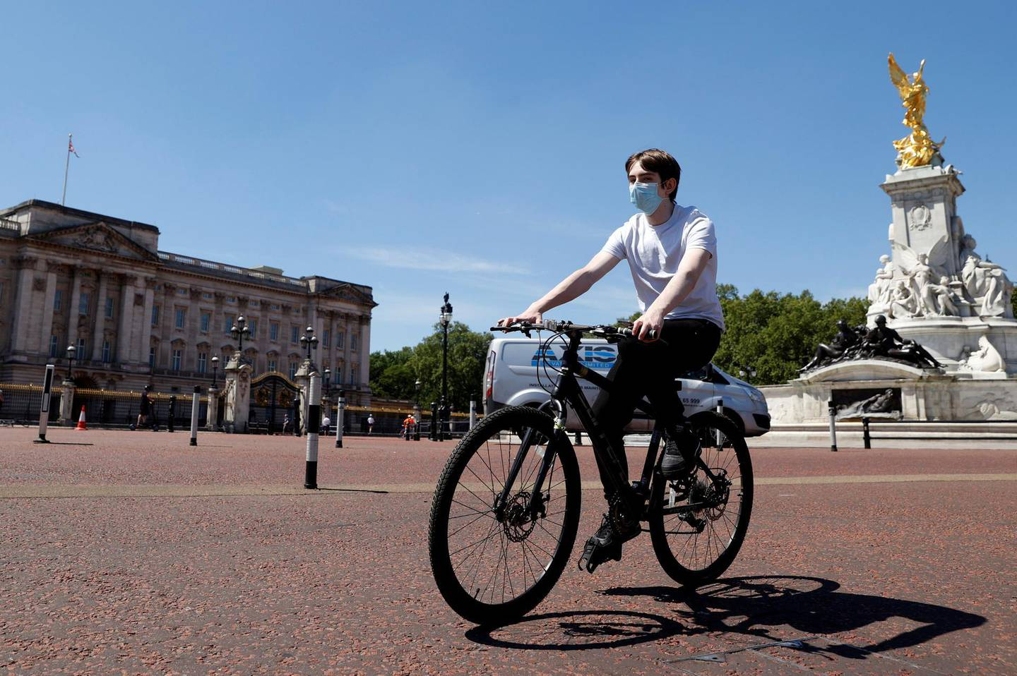 A man wearing a protective face mask cycles past Buckingham Palace, following the outbreak of the coronavirus disease (COVID-19), London, Britain, May 21, 2020. REUTERS/John Sibley