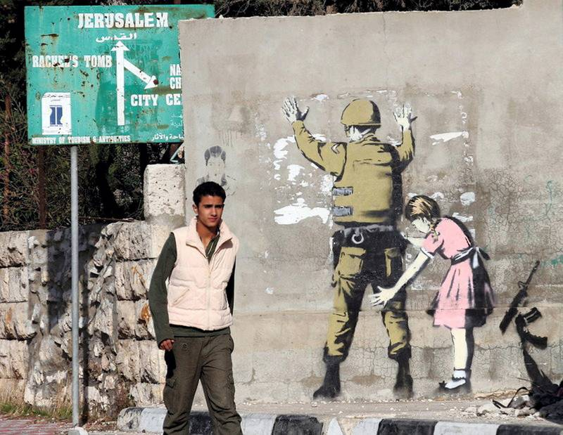 epa01191235 Illusive British graffiti artist named Banksy has painted new works in the West Bank town of Bethlehem, including a stencil work showing a small girl in a dress (a Palestinian?) frisking a soldier (an Israeli?) painted on a wall a Palestinian teenager passes by in the West bank town of Bethlehem, 04 December 2007. The works are not signed.  EPA/JIM HOLLANDER *** Local Caption *** 01191235