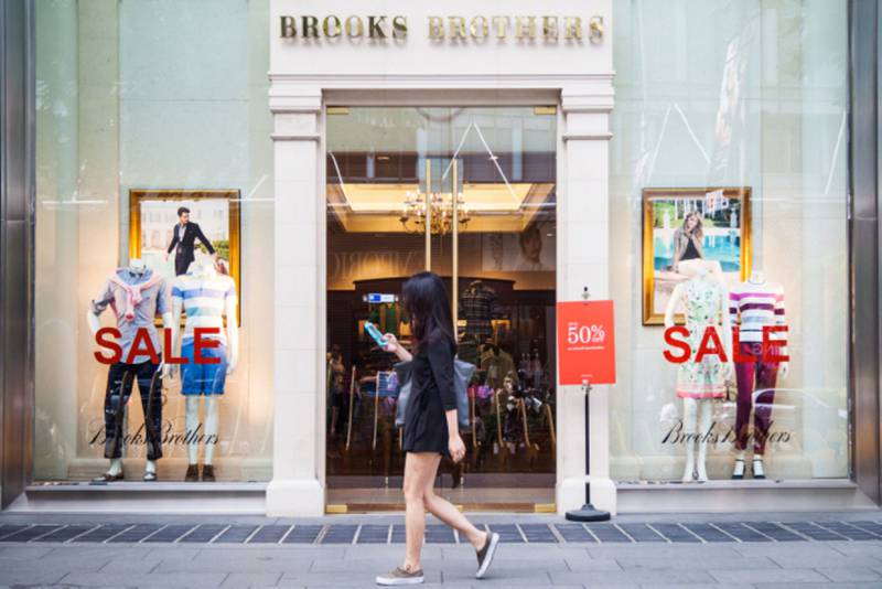 A pedestrian uses a mobile device as she walks past sale signs in a Brooks Brothers Inc. store on Orchard Road in Singapore, on Sunday, June 21, 2015. Consumer prices prices declined for a sixth straight month in April and employment contracted last quarter for the first time since 2009. Photographer: Nicky Loh/Bloomberg