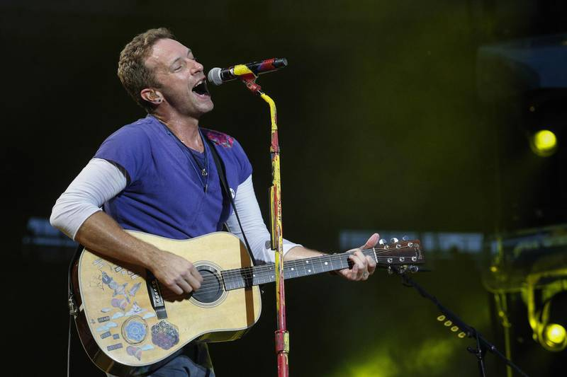 Lead singer of British band Coldplay Chris Martin performs at the Stade de France Arena in Saint Denis, on the outskirts of Paris, on July 15, 2017.  / AFP PHOTO / GEOFFROY VAN DER HASSELT / RESTRICTED TO EDITORIAL USE