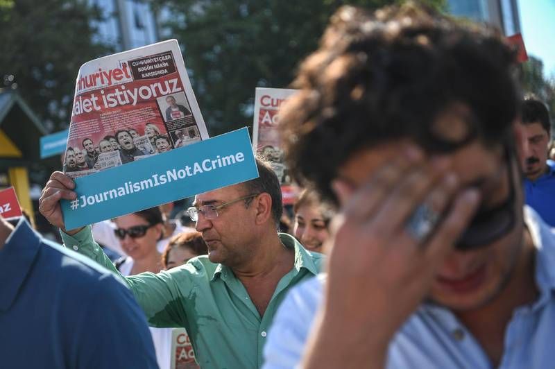 """Journalists hold  banners and copies of Cumhuriyet daily reading """"We want Justice"""" as they march to the courthouse from Cumhuriyet daily's headquarters on July 24, 2017 in Istanbul. Seventeen directors and journalists from one of Turkey's most respected opposition newspapers go on trial on July 24 after spending over eight months behind bars in a case which has raised new alarm over press freedoms under President Recep Tayyip Erdogan. / AFP PHOTO / OZAN KOSE"""