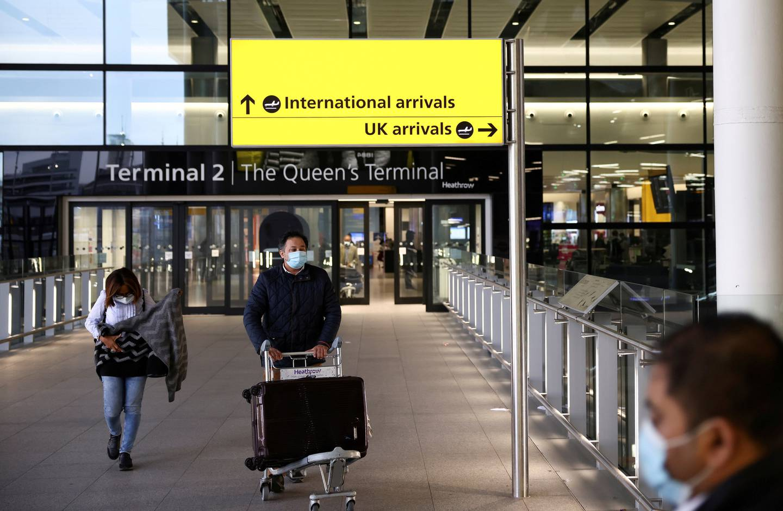 FILE PHOTO: Travellers walk through Terminal 2 at Heathrow Airport, amid the coronavirus disease (COVID-19) outbreak in London, Britain February 14, 2021. REUTERS/Henry Nicholls//File Photo