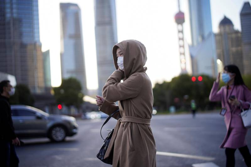 People wear protective face masks, following an outbreak of the novel coronavirus disease (COVID-19), at Lujiazui financial district in Shanghai, China March 19, 2020. REUTERS/Aly Song