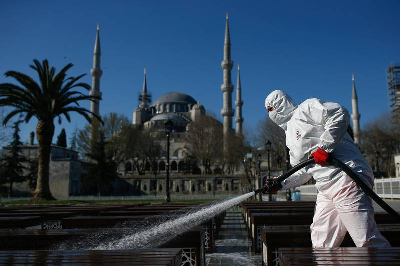 A municipality worker wearing a face mask and protective suits disinfects chairs outside the the historical Sultan Ahmed Mosque, also known as Blue Mosque, amid the coronavirus outbreak, in Istanbul, Saturday, March 21, 2020.  The new COVID-19 coronavirus can cause mild or moderate symptoms, but for some it can cause severe illness. (AP Photo/Emrah Gurel)