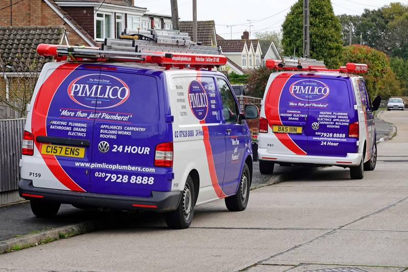2DB29J9 Pimlico plumbers group service business vans outside home vehicle graphics advertising company care services for property maintenance work England UK