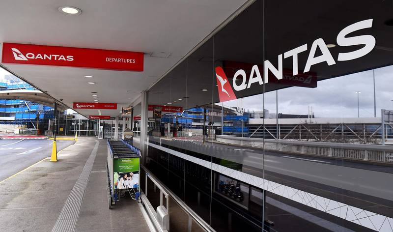 """Baggage trolleys are seen outside the Qantas terminal at Melbourne Airport on August 20, 2020. Australian flag carrier Qantas on August 20, 2020 posted an almost 2 billion USD annual loss after a """"near-total collapse"""" in demand due to the COVID-19 coronavirus pandemic. / AFP / William WEST"""