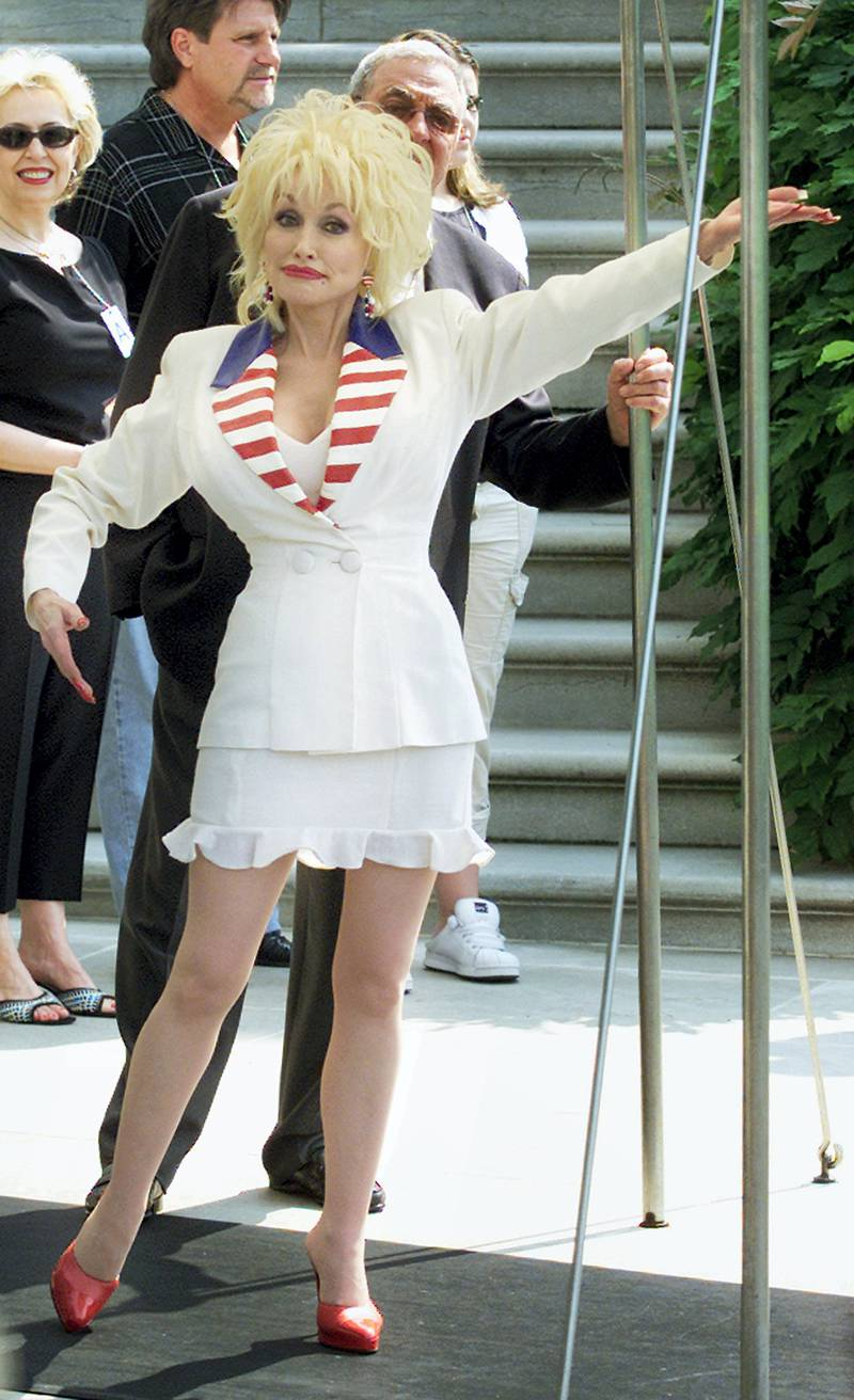 Singer Dolly Parton motions to the press on the South Grounds of the White House in Washington, July 4, 2003. Parton will perform tonight on the west front of the U.S. Capitol Building. REUTERS/William Philpott  WP/GAC